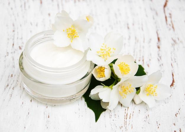 Idratanti crema viso e corpo con fiori di gelsomino su fondo di legno bianco Foto Premium