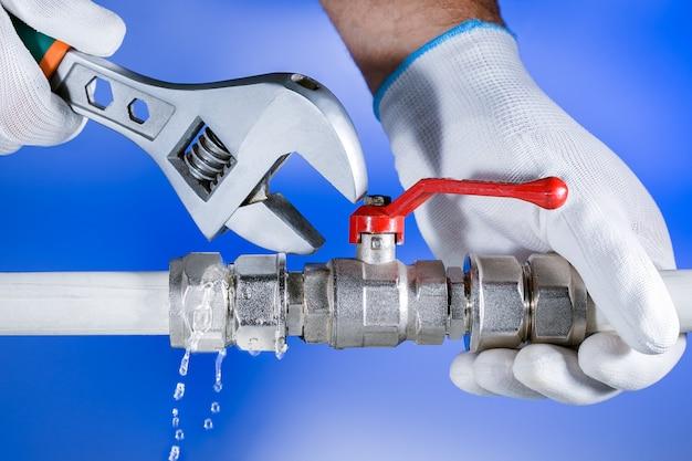 Idraulico delle mani sul lavoro in un bagno, servizio di riparazione dell'impianto idraulico. perdita d'acqua. riparare l'impianto idraulico. Foto Premium