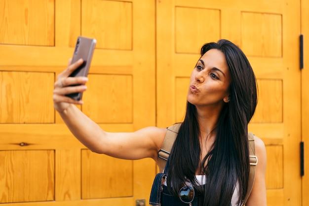 Il bacio di salto della donna graziosa che prende la ragazza della foto di selfie fa l'autoritratto all'aperto. Foto Premium