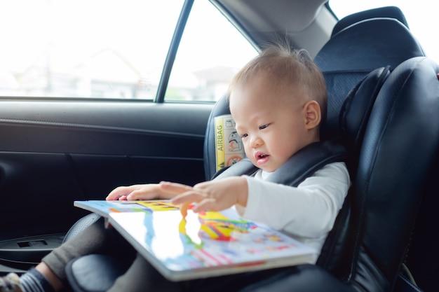 Il bambino asiatico che si siede nella sede di automobile che tiene e gode del libro di lettura Foto Premium