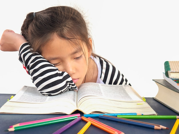Il bambino asiatico sta dormendo mentre legge un grande libro Foto Gratuite