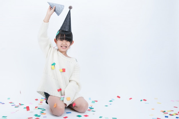 Il bambino che indossa un cappello da festa nero si sta divertendo. sfondo bianco e cappello nero vanno bene insieme. Foto Premium