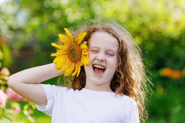 Il bambino con i girasoli nella sua mano mostra i denti bianchi Foto Premium