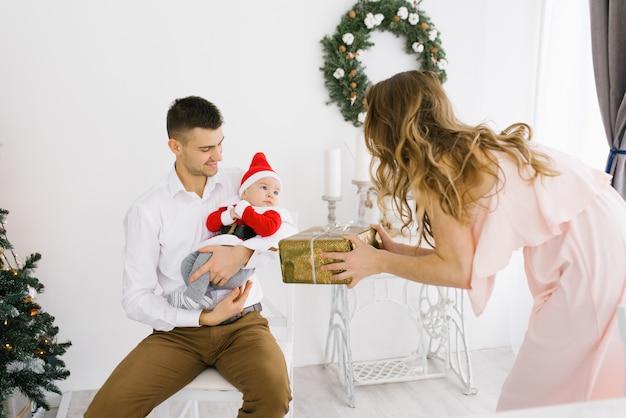 Il bambino con il costume di una piccola santa tra le braccia di papà e la mamma gli fa un regalo di natale in salotto, decorato per le vacanze di capodanno Foto Premium