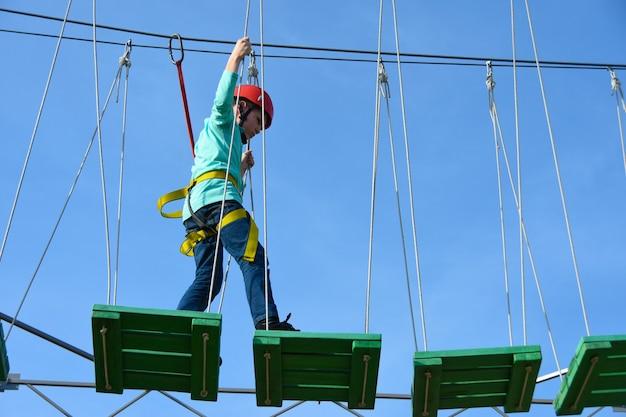 Il bambino del ragazzo fa un passo sui bordi di legno sulla corsa ad ostacoli in un parco di divertimenti Foto Premium