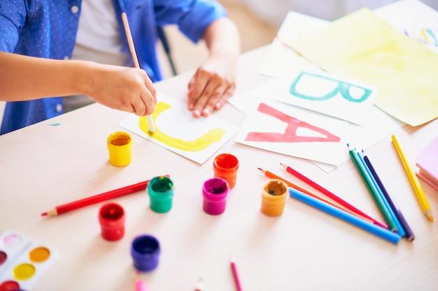 Il bambino disegna con un pennello acquerelli su carta la lettera c Foto Premium