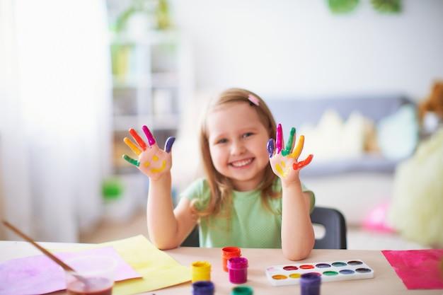Il bambino divertente mostra ai loro palmi la pittura dipinta. Foto Premium