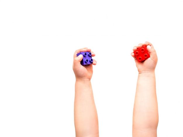 Il bambino è holidng viola e blocchi di costruttore rosso nei pugni. Foto Premium