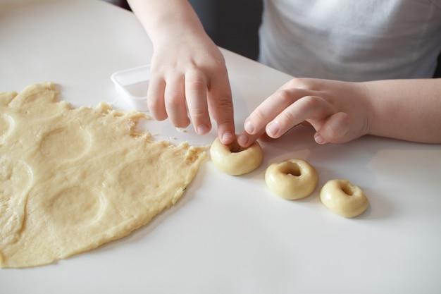 Il bambino fa stampi per biscotti su un tavolo bianco. preparazione di dolci fatti in casa avvicinamento Foto Premium