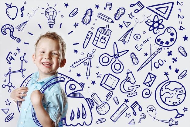 Il bambino felice in una camicia leggera va a scuola per la prima volta. Foto Premium