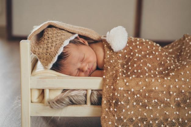 Il bambino giace su un letto di legno sotto una coperta. Foto Premium