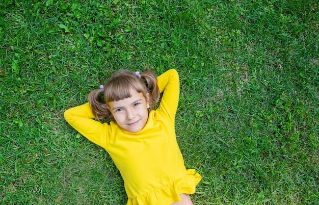 Il bambino giace sull'erba. Foto Premium