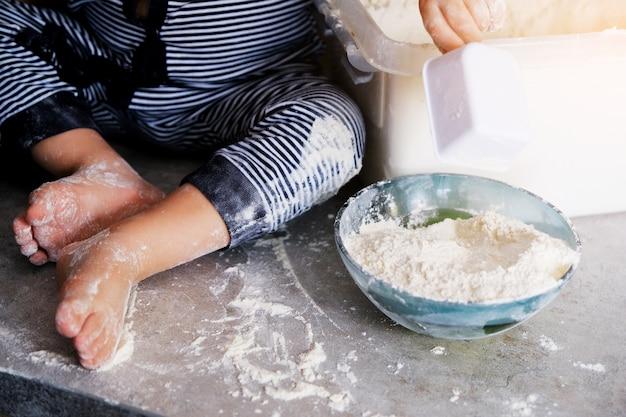Il bambino gioca e si diletta sul tavolo della cucina. le gambe dei bambini sono macchiate di farina bianca. Foto Premium