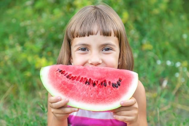 Il bambino mangia un'anguria nel giardino Foto Premium