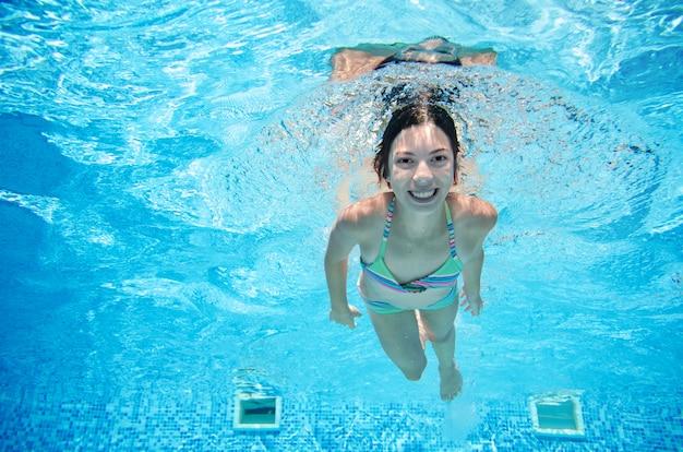 Il bambino nuota in piscina sott'acqua, la felice ragazza attiva in occhiali si diverte in acqua, lo sport per bambini in vacanza con la famiglia Foto Premium