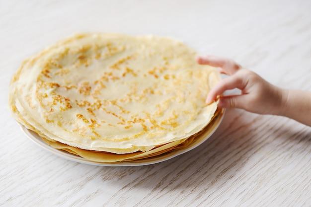 Il bambino prende un pancake da un piatto con i pancake Foto Premium
