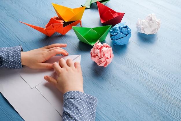 Il bambino produce origami da carta colorata Foto Premium