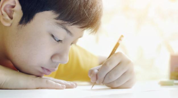 Il bambino scrive i compiti. i bambini a fare lavori a casa sul tavolo in salotto Foto Premium