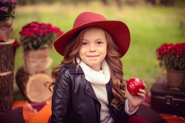 Il bambino sorridente con il cestino delle mele rosse che si siedono in autunno parcheggia Foto Premium