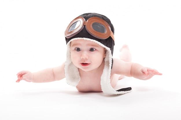 Il bambino sorridente sveglio nuda nel cappuccio del pilota sta volando Foto Premium