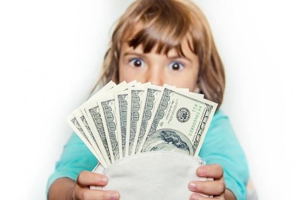 Il bambino tiene i soldi nelle sue mani. messa a fuoco selettiva Foto Premium