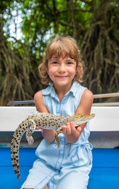 Il bambino tiene in mano un piccolo coccodrillo. Foto Premium