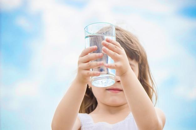 Il bambino tiene un bicchiere d'acqua nelle sue mani. messa a fuoco selettiva. Foto Premium