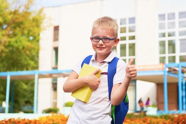 Il bambino va alla scuola elementare. ritratto di un bambino felice con una valigetta sulla schiena. Foto Premium