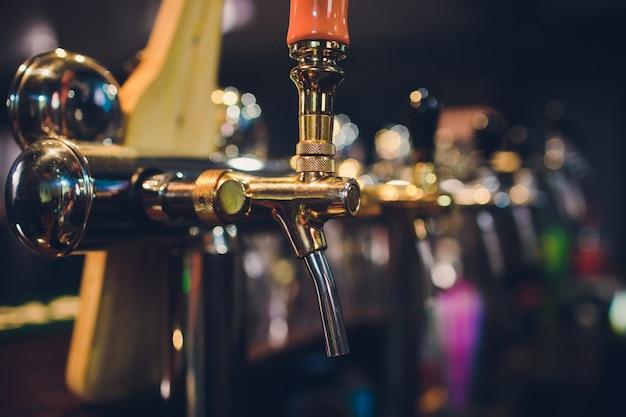Il bancone del bar con bottiglie e apparecchi per l'erogazione della birra. apparato per l'erogazione di birra al bar. pub. il bar nel ristorante. apparato per l'erogazione di birra in un ristorante. Foto Premium