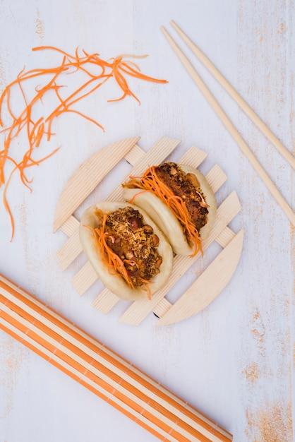 Il bao asiatico del gua è servito sul piatto di legno circolare con le bacchette e la carota grattata su superficie di legno Foto Gratuite