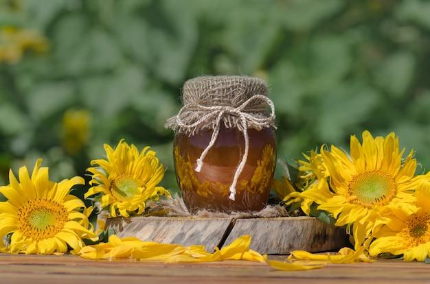 Il barattolo del miele ed il bastone di legno sulla tavola contro verde hanno offuscato naturale Foto Premium