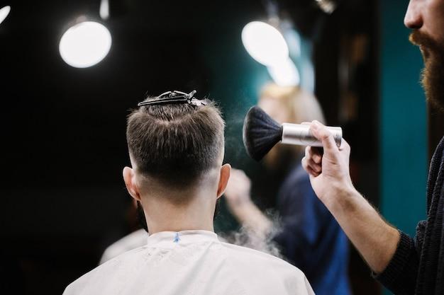 Il barbiere copre la testa dell uomo con polvere