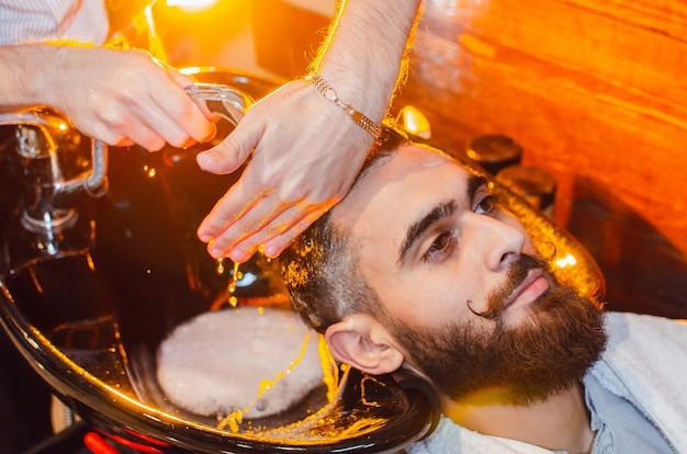 Il barbiere lava la testa di un bel ragazzo con barba e baffi nel lavandino Foto Premium