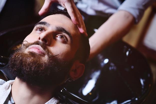 Il barbiere o il parrucchiere lavano la testa del cliente Foto Premium