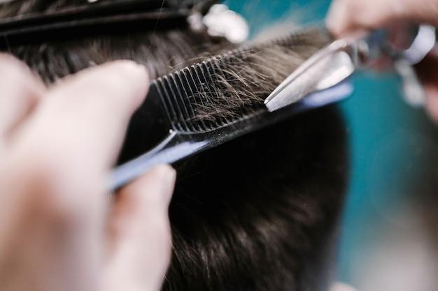 Il barbiere taglia i capelli dell'uomo con forbici Foto Gratuite
