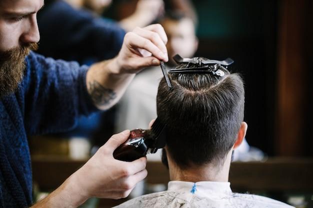Il barbiere taglia i capelli dell'uomo con il tagliatore e ...