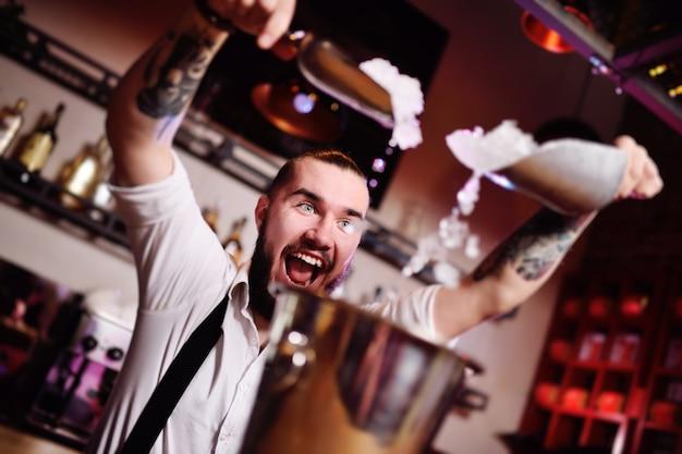 Il barista ad una festa in un night club versa il ghiaccio per cocktail e urla felicemente contro il bar Foto Premium