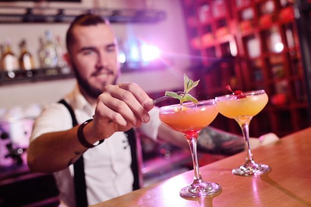 Il barista bello prepara un cocktail alcolico all'arancia e sorride di un bar o di un night club Foto Premium