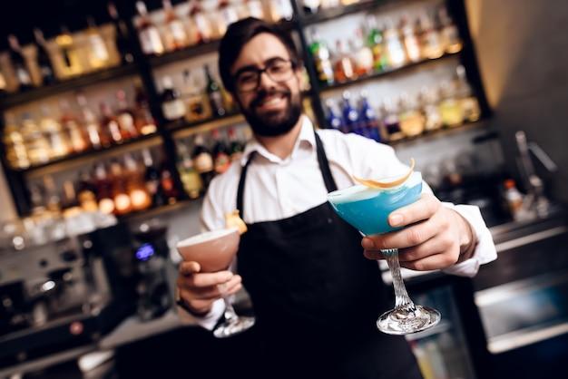 Il barista con la barba preparò un cocktail al bar. Foto Premium