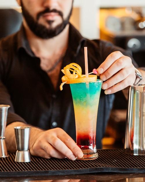 Il barista decora il cocktail colorato con la scorza d'arancia Foto Gratuite