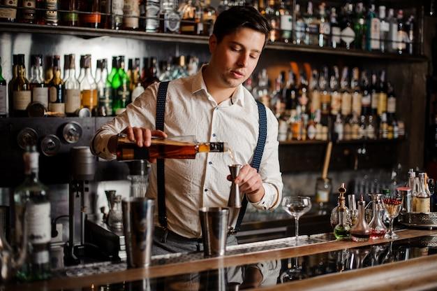 Il barista in camicia bianca sta preparando un cocktail alcolico Foto Premium