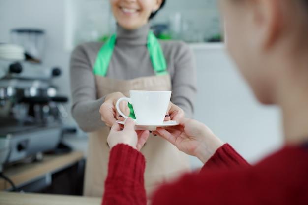 Il barista in grembiule nella caffetteria dà appena preparato il caffè fresco al cliente Foto Premium