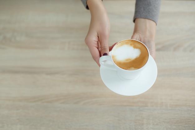 Il barista in grembiule nella caffetteria offre al cliente caffè appena preparato Foto Premium