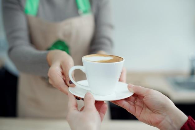 Il barista nella caffetteria dà appena preparato caffè fresco al cliente Foto Premium