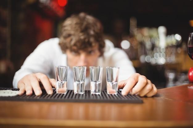 Il barista prepara e fodera i bicchierini per le bevande alcoliche sul bancone del bar Foto Gratuite