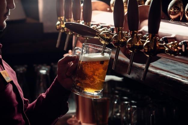 Il barista riempie il boccale di birra dal rubinetto della birra Foto Gratuite