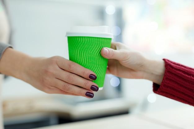 Il barista sta dando del caffè caldo in un bicchiere di carta da asporto verde al cliente. il caffè porta via al negozio di caffè Foto Premium