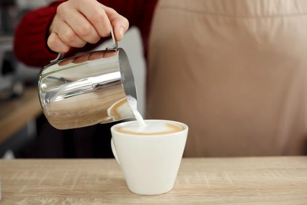 Il barista versa il latte dal vaso del metallo alla tazza di vetro bianca sulla tavola di legno latte pronto Foto Premium