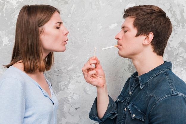 Il bastone di salto della corrispondenza della donna tiene dalla sua sigaretta di trasporto del ragazzo in bocca Foto Gratuite