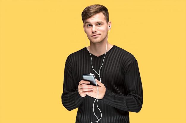 Il bel giovane in piedi e ascoltare musica. Foto Gratuite